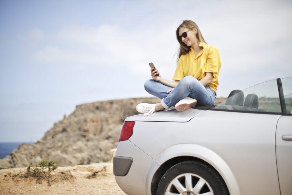 Woman sat on car at the coast