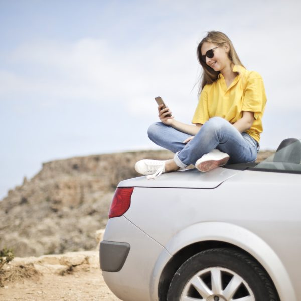 Woman sat on car at the coast