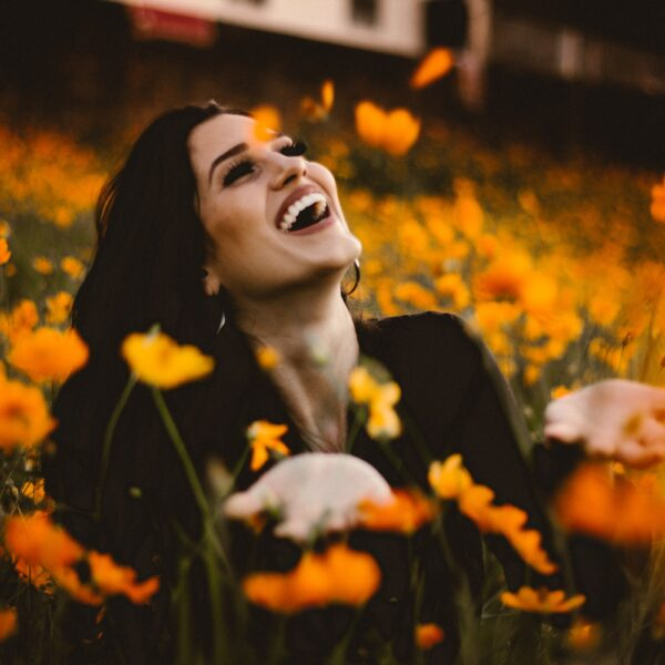 Woman smiling surrounded by flowers