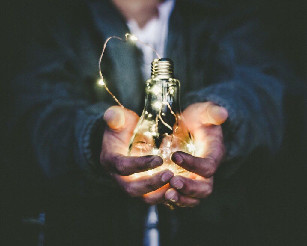 Man holding incandescent light bulb