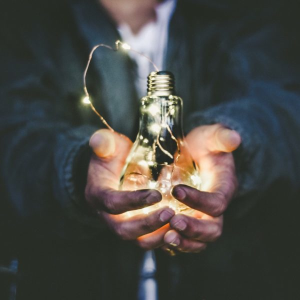 Man holding incandescent light bulb