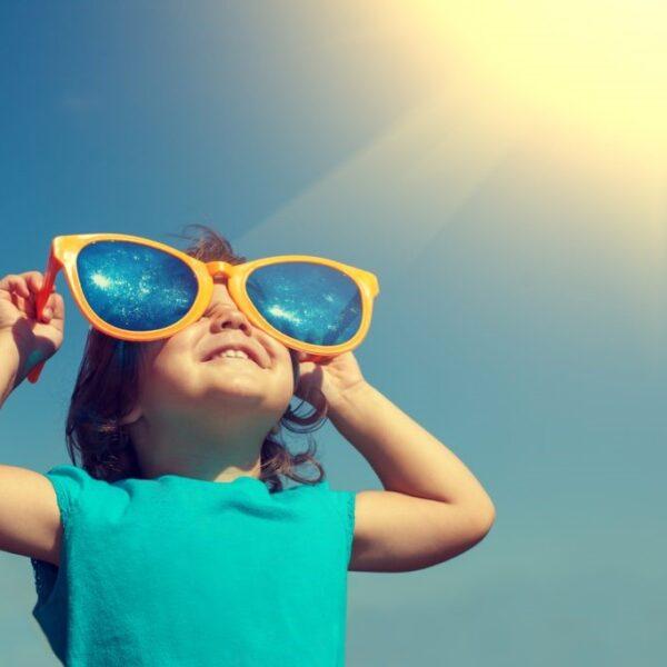 Child holding oversized sunglasses over their eyes