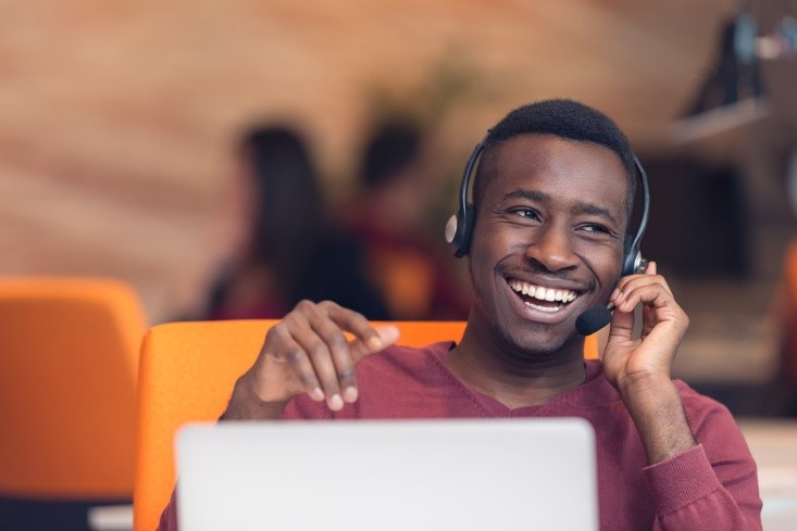 Man smiling whilst using headset