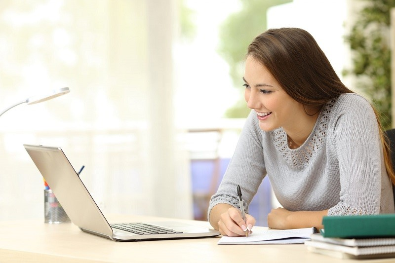 Woman smiling whilst copying information down from a laptop