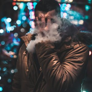 Man holding face whilst vaping