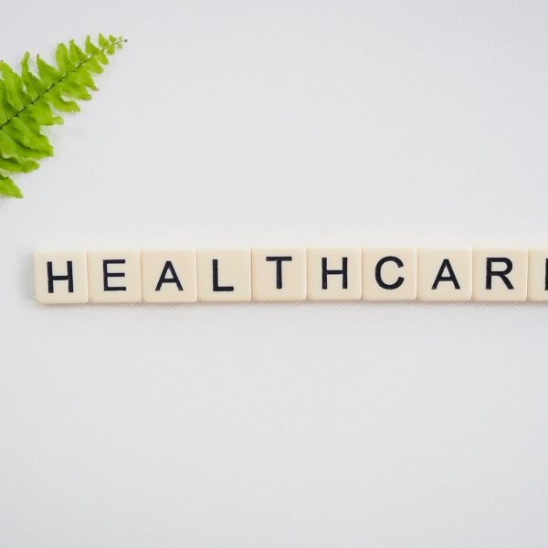 Scrabble pieces spelling out 'healthcare' next to a leaf