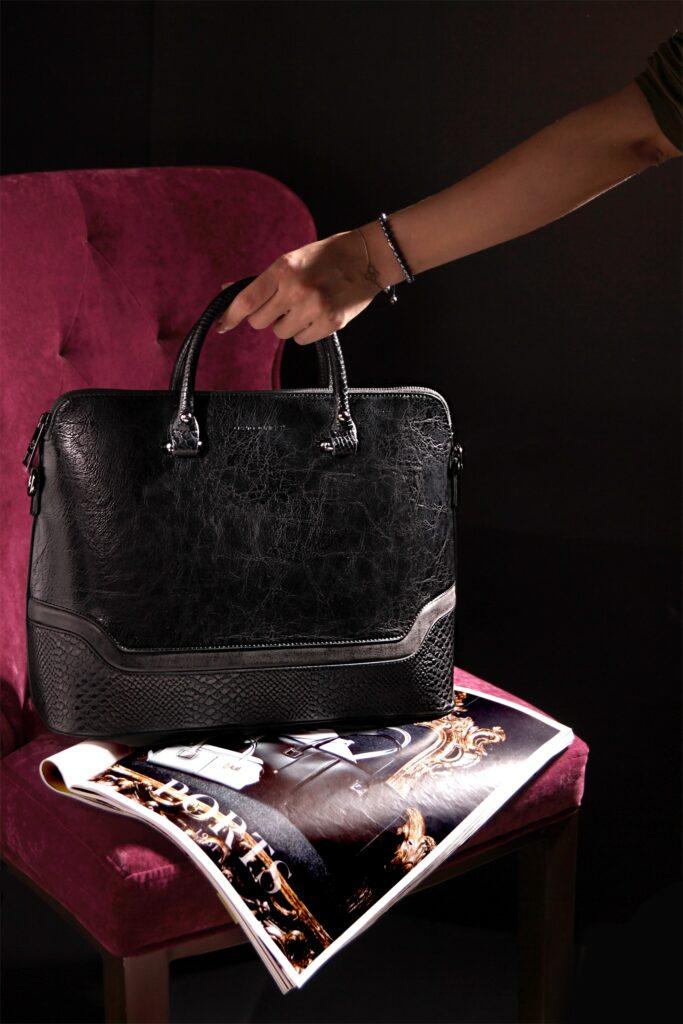 Black leather handbag on a seat