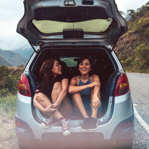 Two women sitting in a hatchback