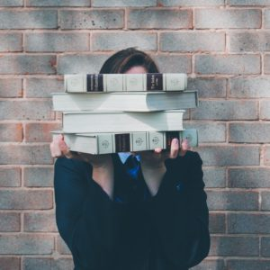 Person holding books in front of their face