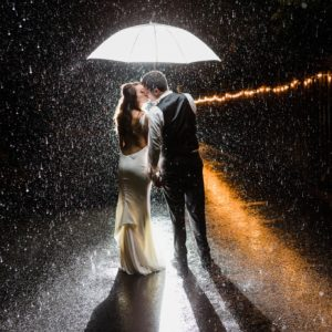 Bride and groom kissing under umbrella in the rain