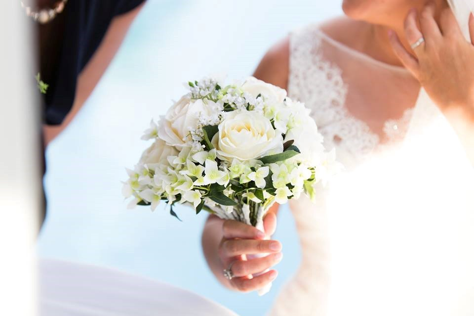 Bride holding flowers and showing ring