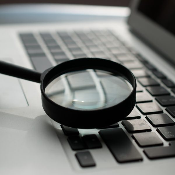 Magnifying glass held over laptop keyboard