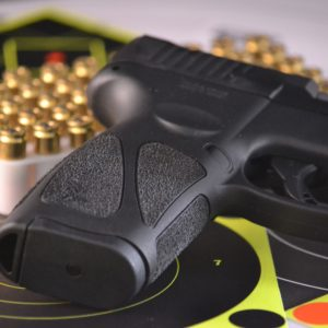 Taurus G3 9mm pistol with targets and bullets in the background