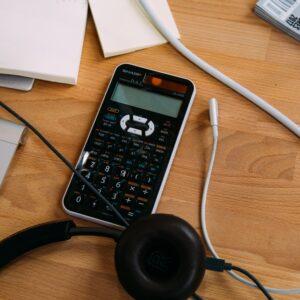 Black Sharp scientific calculator and headphones on a desk