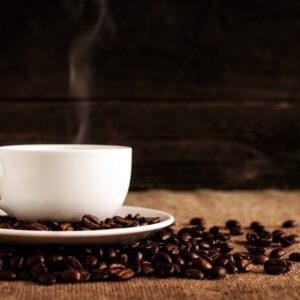 Mug of coffee on a saucer next to coffee beans