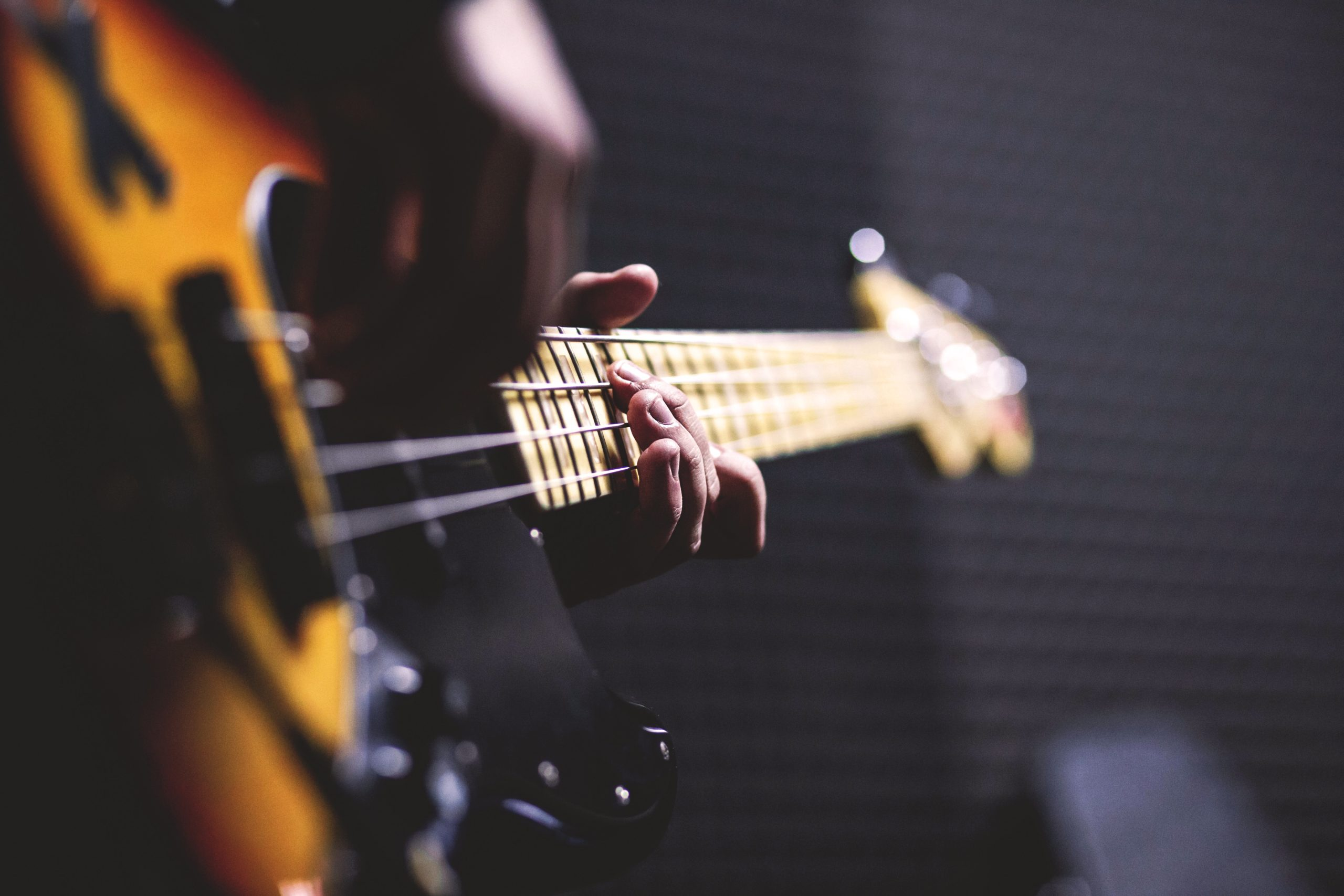 Person playing sunburst finish electric bass