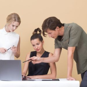 Two women and a man looking at a laptop