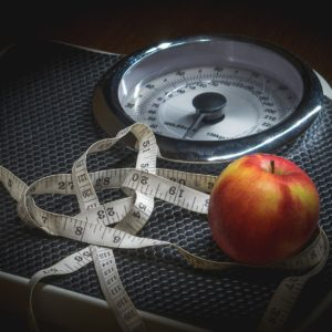 Tape measure and apple on scales