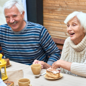 Elderly couple enjoying cake at table