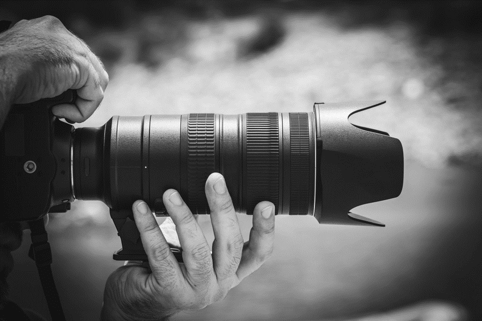 Person supporting camera lens