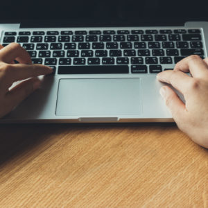 Hands typing on notebook computer