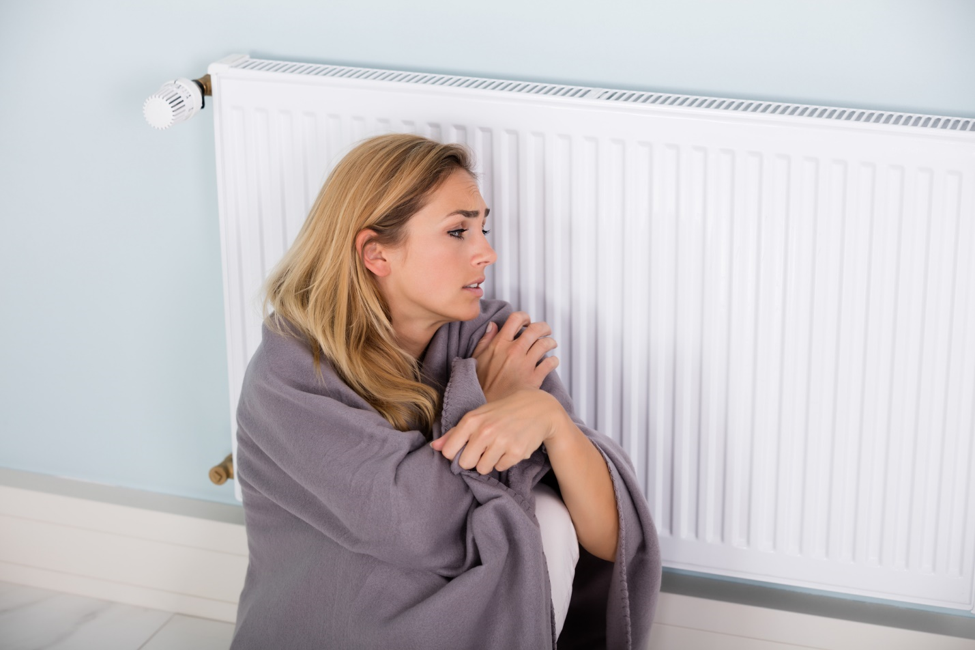 Woman wrapped in a blanket next to radiator