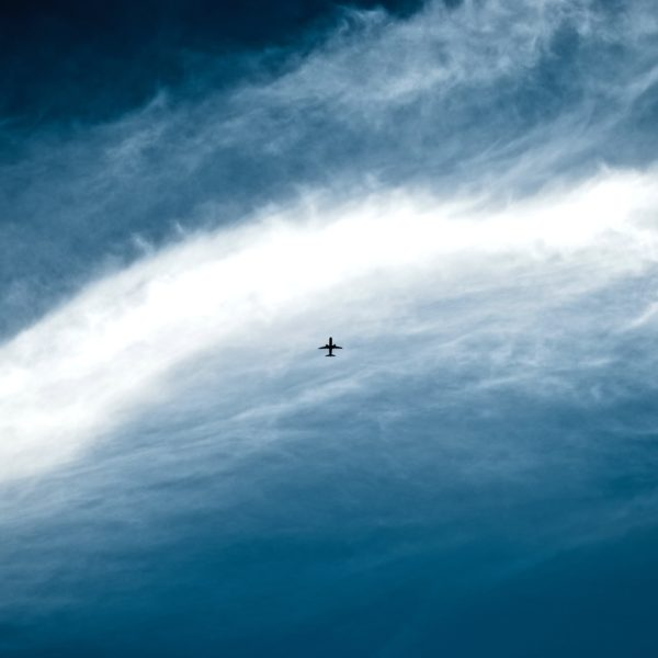Plane silhouette among clouds