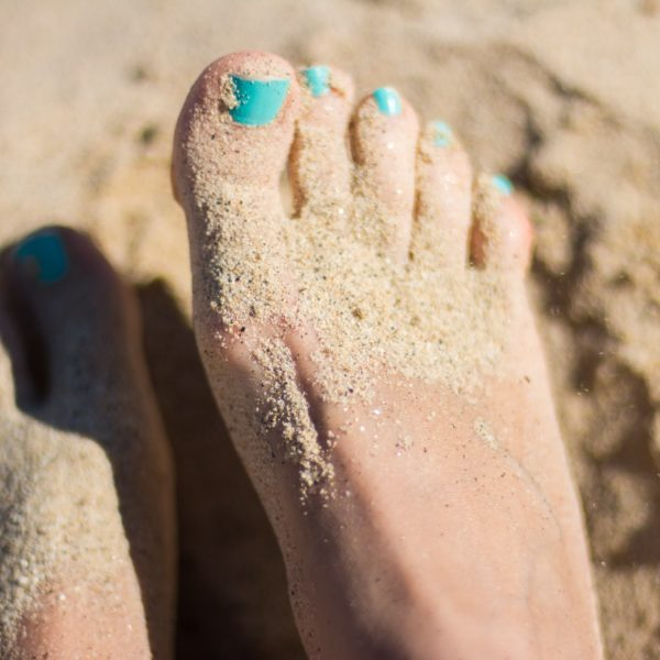 Feet with painted nails covered in sand