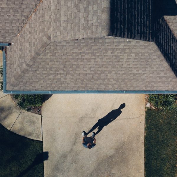 Aerial view of a roof and a man in front of house