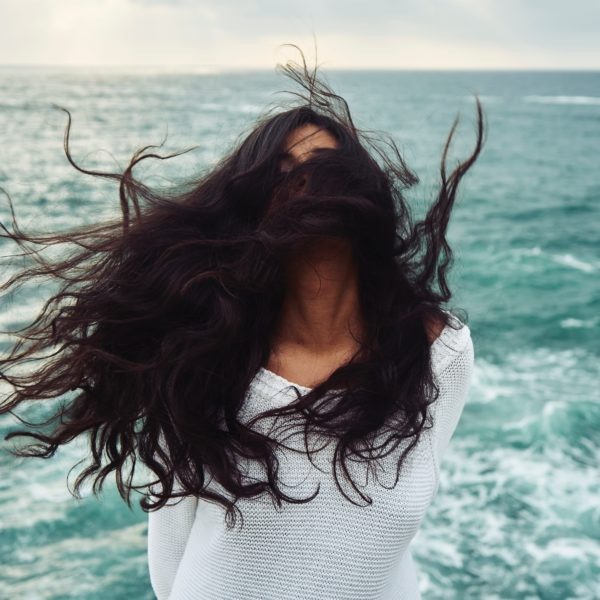 Woman standing near water with her hair being blown into her face