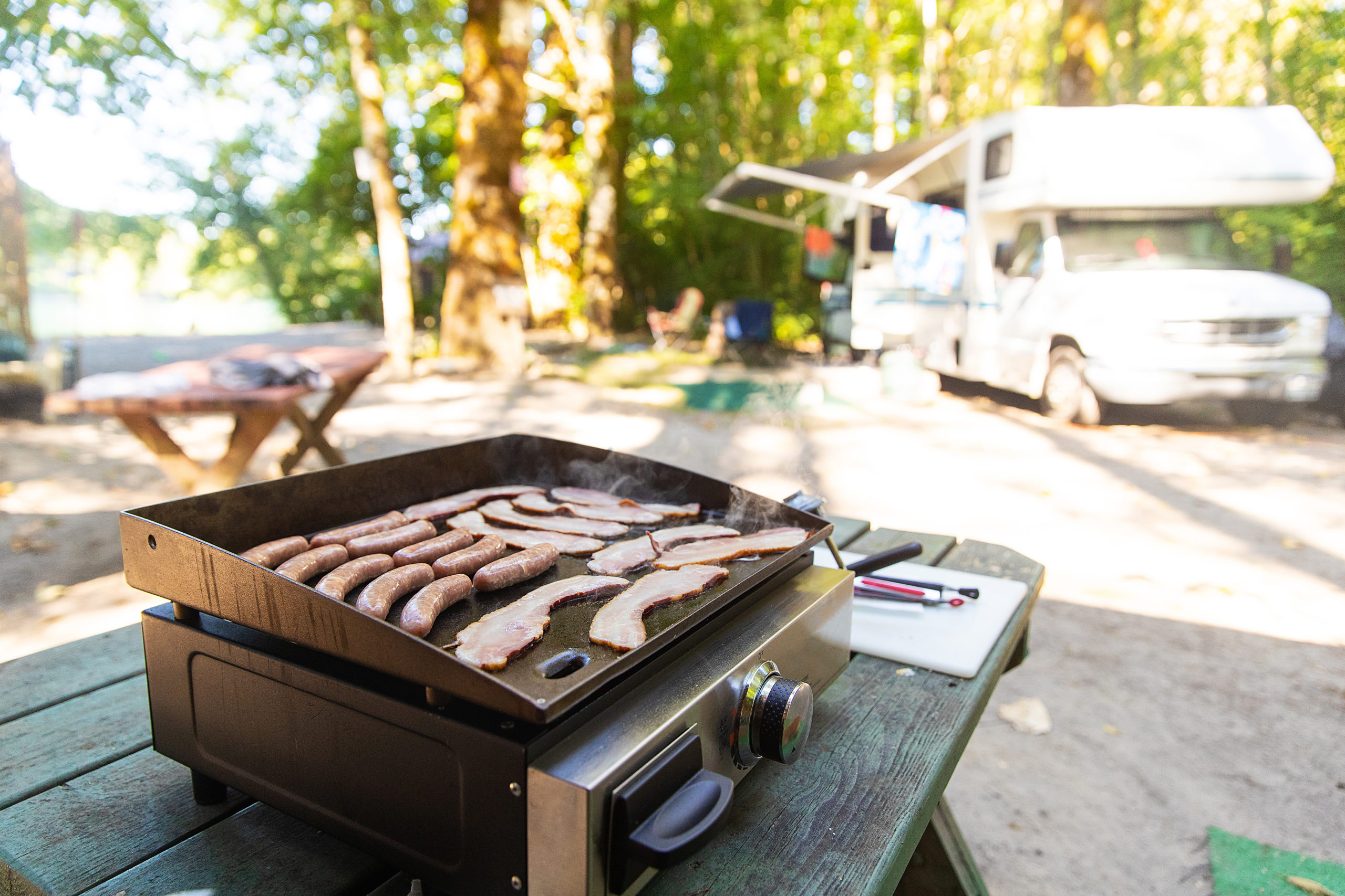 Bacon and sausage on a flat grill at a camp site