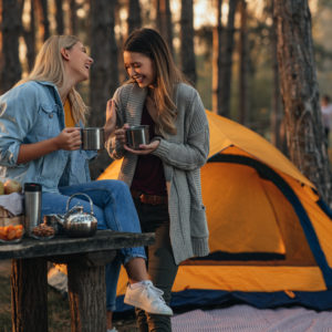 Young women enjoying hot drink at the forest during autumn weekend