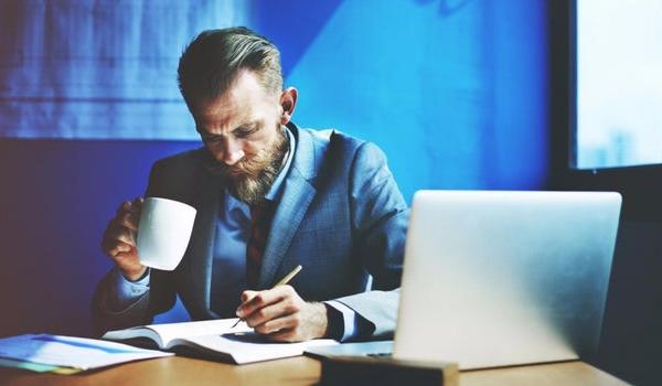 Man drinking coffee whilst working on paperwork