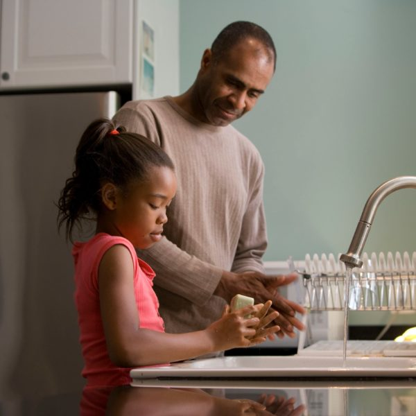 Father teaching daughter how to wash her hands