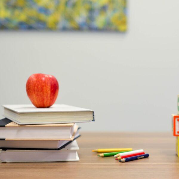 A teacher's desk with books, an apple, pencils, and ABC blocks