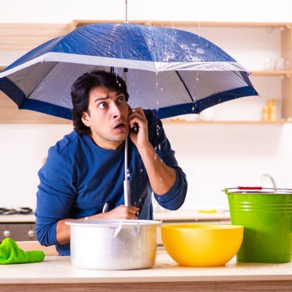 Man under umbrella using a phone indoors