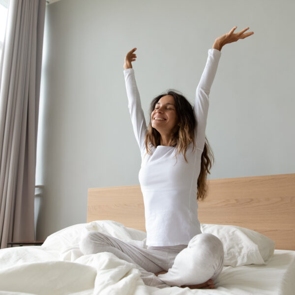 Woman stretching arms on bed
