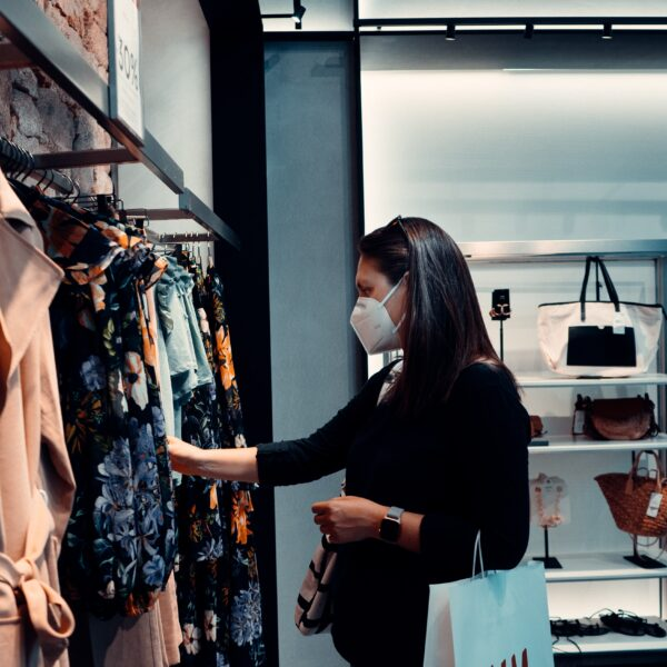 Woman shopping for clothes whilst wearing a face mask