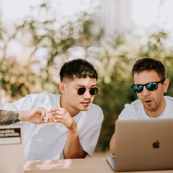 Two men using MacBooks
