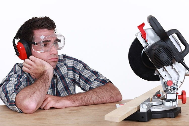 Man looking at a mitre saw