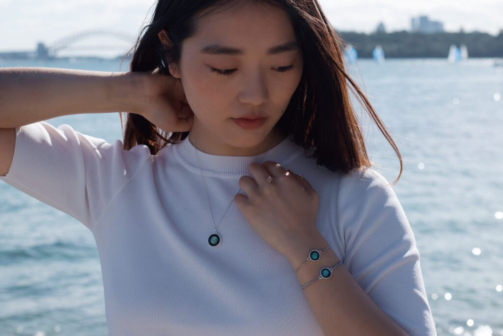 Woman modelling for a jewellery photoshoot for Moonglow Australia at Milk Beach, Sydney, Australia