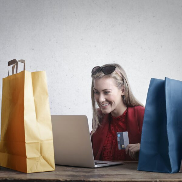 Woman surrounded by shopping bags buying something on laptop