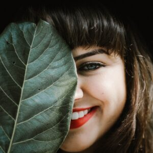 Woman smiling from behind a leaf