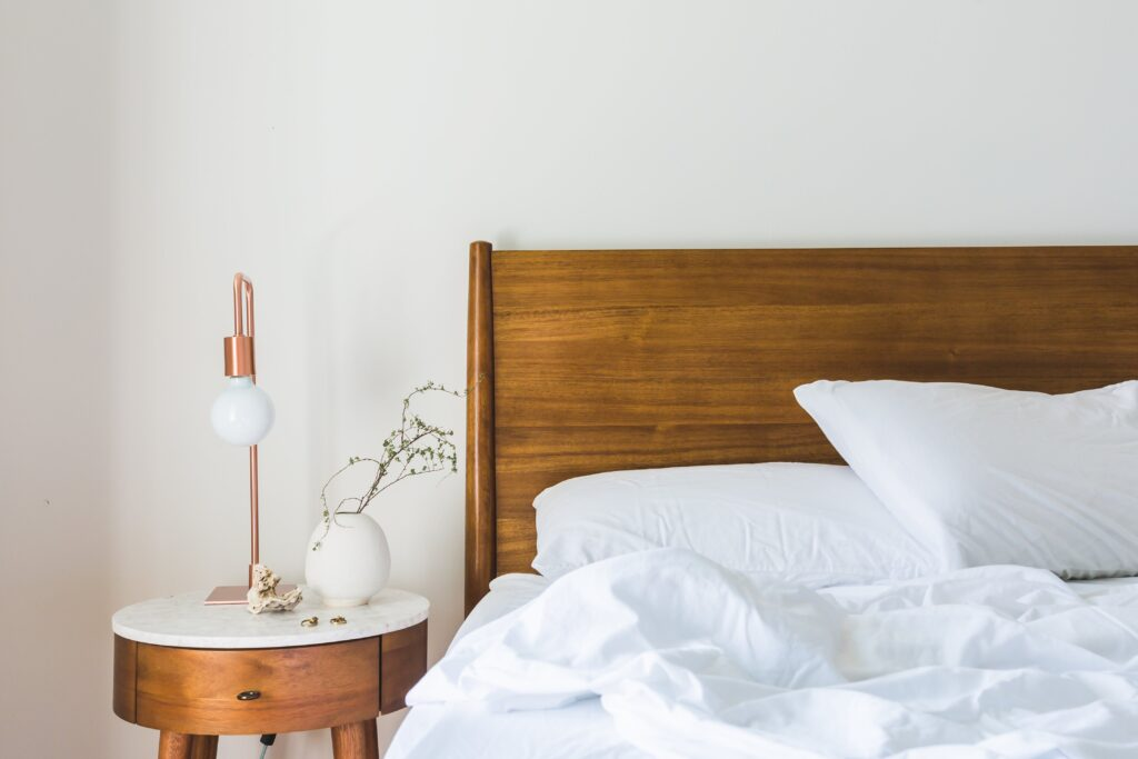 White bedspread, beside nightstand with a copper table lamp on it