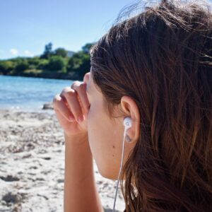 Woman meditating on beach whilst listening to music
