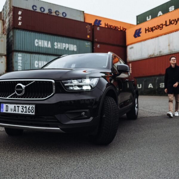 Young man standing behind a Volvo SUV Car XC40 in the Harbour of Düsseldorf