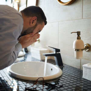 Man washing his face over sink