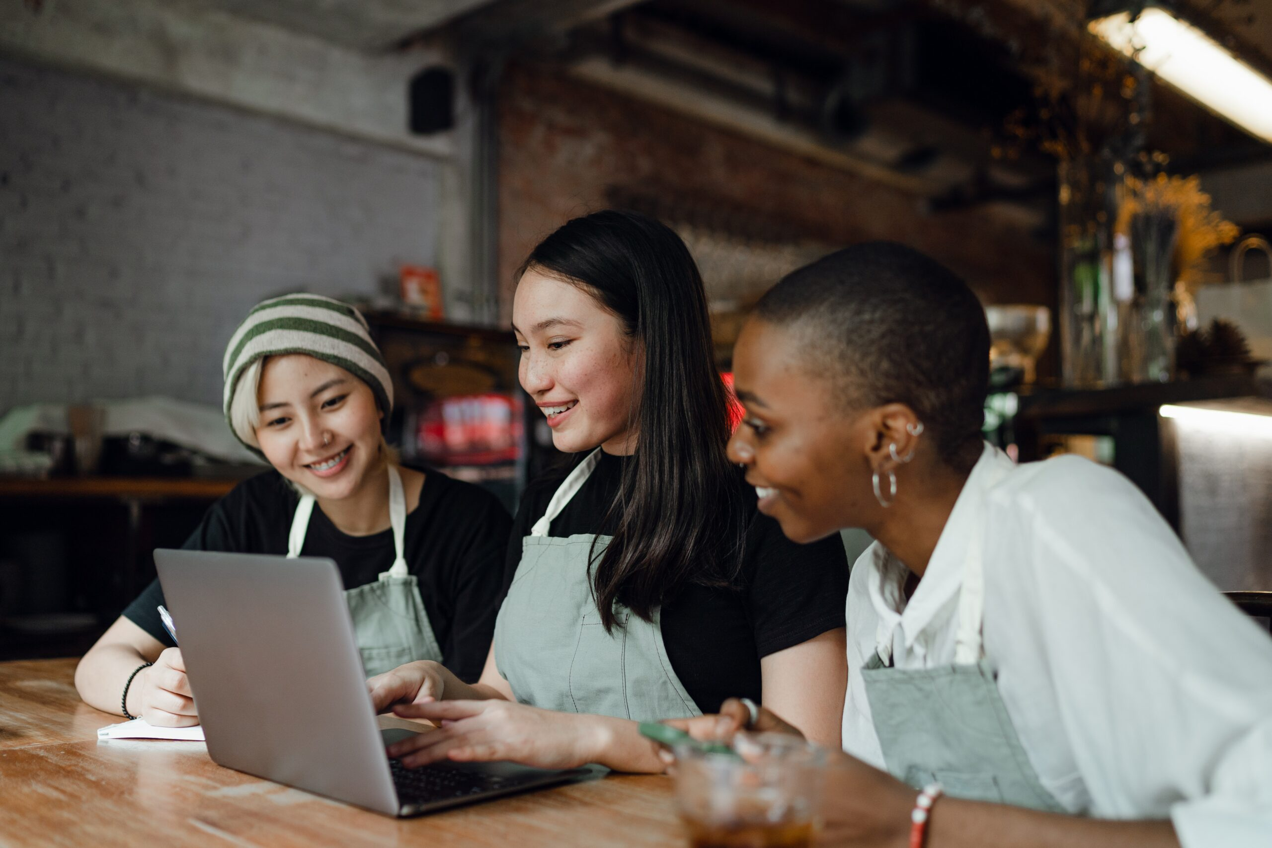 Three women using a laptop together in a café