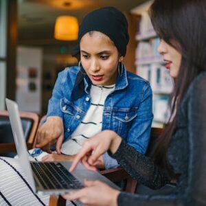 Two women using a MacBook
