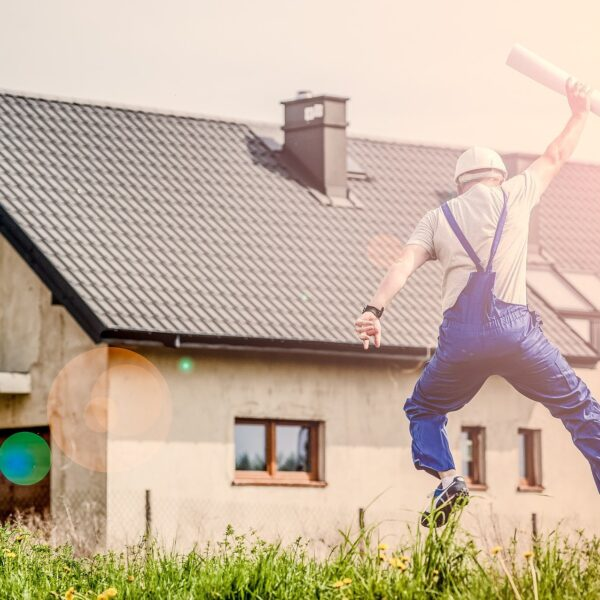 Architect jumping in front of a house